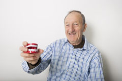 Il ritratto dei denti sorridenti della tenuta dell'uomo senior modella contro fondo grigio Fotografia Stock Libera da Diritti
