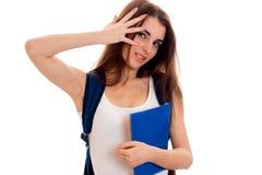 Il ritratto dei giovani dispiaceva la ragazza castana dello studente con lo zaino sulle suoi spalle e libri in sue mani isolate s Immagine Stock