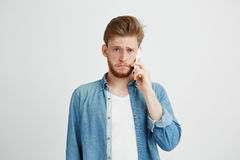 Il ritratto dei giovani ha rovesciato l'uomo che parla sul telefono che esamina la macchina fotografica sopra fondo bianco Fotografie Stock Libere da Diritti
