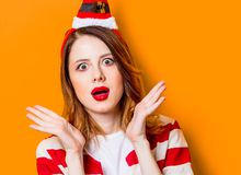 Il ritratto dei giovani ha sorpreso la donna della testarossa in cappello di Santa Claus immagine stock libera da diritti