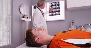 Il ritratto dei giovani mette in mostra l'atleta che si riposa mentre esami di medico Immagine Stock