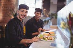 Il ritratto dei giovani sorridenti aspetta il personale che si siede con l'alimento e la lavagna per appunti al contatore Immagini Stock Libere da Diritti
