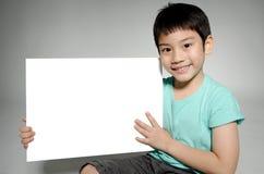 Il ritratto del bambino asiatico con il piatto in bianco per aggiunge il vostro testo Fotografie Stock