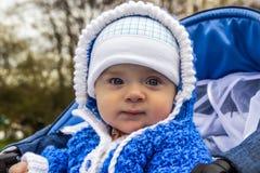 Il ritratto del bambino sveglio con l'angelo osserva la seduta in passeggiatore L'età del bambino è di 6 mesi Immagini Stock Libere da Diritti
