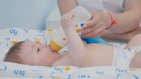 Il ritratto del bambino sveglio succhia la miscela dalla bottiglia archivi video