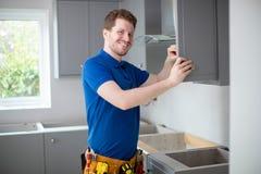 Il ritratto del carpentiere Installing Luxury Modern misura la cucina immagine stock libera da diritti