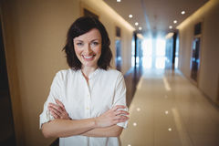 Il ritratto del dirigente femminile che sta con le armi ha attraversato in corridoio Immagini Stock