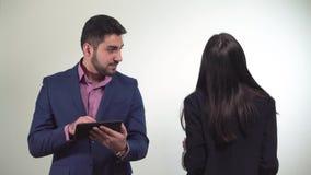Il ritratto del giovane dei soci commerciali che tiene una compressa nelle mani ed in donna sta ballando accanto lui archivi video