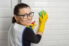 Il ritratto del lavoratore di servizio di pulizia che indossa i guanti di gomma protettivi, tenendo la spugna ed il detersivo, co fotografia stock
