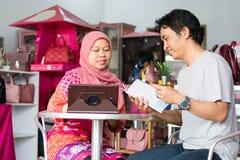 Il ritratto del marito musulmano asiatico di medio evo e la moglie discutono circa l'affare nel loro deposito fotografia stock