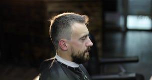 Il ritratto del mezzo ha invecchiato l'uomo in lampadina ad un parrucchiere stock footage