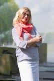 Il ritratto del mezzo maturo ha invecchiato gli occhiali d'uso sorridenti della donna bionda che posano all'aperto nel parco Fotografie Stock
