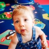 Il ritratto del neonato sorridente caucasico biondo adorabile sveglio con marrone osserva in pagliaccetto blu che si siede sul pa Fotografia Stock