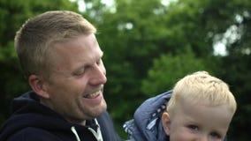Il ritratto del padre felice gioca con il figlio sveglio di un anno in foresta video d archivio