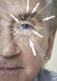 Il ritratto del primo piano dell'uomo d'affari con le cifre binarie e la freccia firma avanzare verso il suo occhio Fotografia Stock
