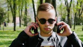 Il ritratto del primo piano dello studente attraente, uomo mette sopra le cuffie che ascolta la musica archivi video
