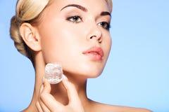 Il ritratto del primo piano di bella giovane donna applica il ghiaccio a fac immagine stock