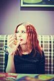 Il ritratto del primo piano di bella giovane donna nel caffè con vino di vetro lo beve Immagini Stock