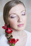 Il ritratto del primo piano di giovane bella donna alla moda con la primavera rossa splendida fiorisce Fotografia Stock