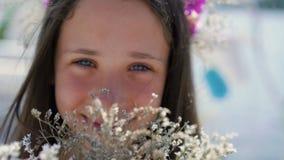 Il ritratto del primo piano del fronte del ` s della ragazza fiuta i fiori lentamente video d archivio