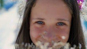 Il ritratto del primo piano del fronte del ` s della ragazza fiuta i fiori lentamente stock footage