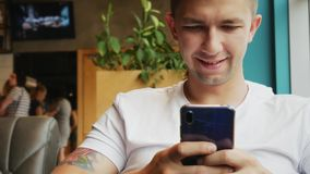 Il ritratto del primo piano del giovane utilizza il telefono cellulare in caffè video d archivio