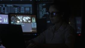 Il ritratto del programmatore della giovane donna che lavora ad un computer nel centro dati ha riempito di schermi di visualizzaz video d archivio