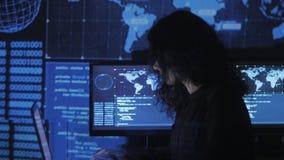 Il ritratto del programmatore della giovane donna che lavora ad un computer nel centro dati ha riempito di schermi di visualizzaz archivi video