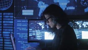 Il ritratto del programmatore della giovane donna in occhiali che funzionano ad un computer nel centro dati ha riempito di scherm video d archivio