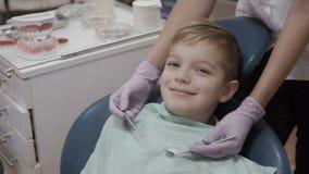 Il ritratto del ragazzino sorridente mostra il pollice su nella sedia del dentista archivi video