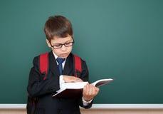 Il ritratto del ragazzo di scuola in vestito nero sul fondo verde della lavagna con lo zaino rosso ha letto il libro, concetto di Fotografia Stock