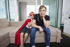 Il ritratto del ragazzo sorridente si è vestito in costume del supereroe che si siede con il padre triste sul letto di sofà a casa fotografia stock