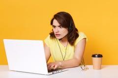 Il ritratto del responsabile concentrato della donna che si siede alla tavola con il computer portatile su fondo giallo in studio fotografie stock