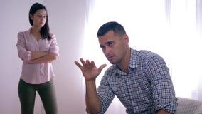 Il ritratto del tipo deludente dopo il litigio con la femmina che si siede a casa piegare passa vicino alla condizione della donn stock footage