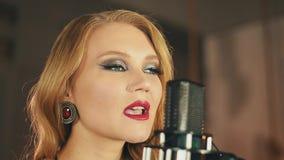 Il ritratto del vocalist con le labbra rosse compone per eseguire al microfono Retro stile video d archivio