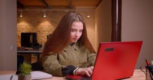 Il ritratto dell'adolescente grazioso che lavora con il computer portatile raggiunge il successo ottiene soddisfatto in ufficio video d archivio