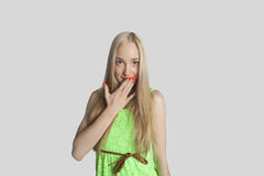 Il ritratto dell'adolescente sorpreso con consegna la bocca sopra fondo grigio fotografia stock