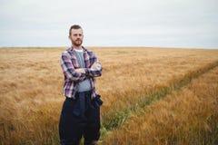 Il ritratto dell'agricoltore che sta con le armi ha attraversato nel campo Fotografia Stock