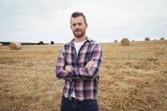 Il ritratto dell'agricoltore che sta con le armi ha attraversato nel campo Fotografie Stock