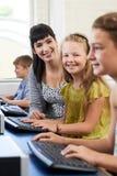 Il ritratto dell'allievo elementare femminile nella classe del computer con insegna a Fotografia Stock Libera da Diritti