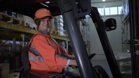 Il ritratto dell'autista di camion femminile felice del carrello elevatore esamina la macchina fotografica ed i sorrisi in magazz stock footage