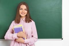 Il ritratto dell'insegnante femminile con i taccuini si avvicina alla lavagna Fotografia Stock