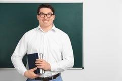 Il ritratto dell'insegnante maschio con i taccuini si avvicina alla lavagna Fotografia Stock