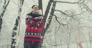 Il ritratto dell'inverno del primo piano della donna in sciarpa del cappello e maglione tricottati di lana alla moda, l'orario in video d archivio