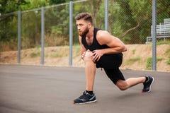 Il ritratto dell'sport barbuti equipaggia l'allungamento delle gambe fuori Fotografie Stock