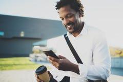 Il ritratto dell'uomo africano americano sorridente in cuffia alla città soleggiata con caffè dentro porta via la tazza e godere  Immagine Stock