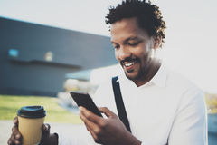 Il ritratto dell'uomo africano americano sorridente in cuffia alla città soleggiata con caffè dentro porta via la tazza e godere  Fotografia Stock Libera da Diritti