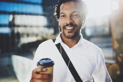 Il ritratto dell'uomo africano americano sorridente in cuffia che cammina alle vie soleggiate con caffè dentro porta via la tazza Immagini Stock Libere da Diritti