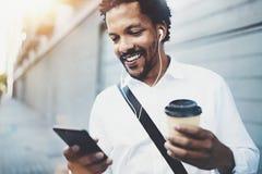 Il ritratto dell'uomo afroamericano sorridente in cuffia che cammina alla città soleggiata con porta via la tazza e godere a musi Fotografia Stock Libera da Diritti