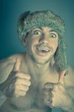 Il ritratto dell'uomo allegro dei pantaloni a vita bassa del giovane fascino con le emozioni pazze, acconsente e sorride, pollice Fotografia Stock Libera da Diritti